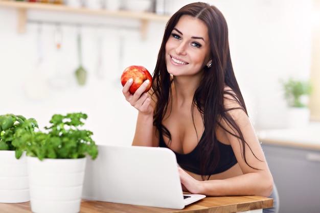 Pasuje uśmiechnięta młoda kobieta z jabłkiem w nowoczesnej kuchni