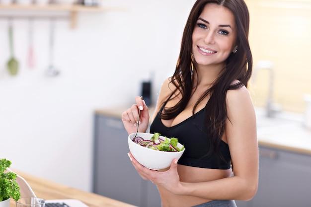 Pasuje uśmiechnięta młoda kobieta z sałatką w nowoczesnej kuchni