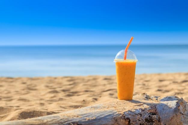 Pasyjny owocowy sok z słomą w szkle na piasek plaży przy phuket tajlandia. koncepcja lato