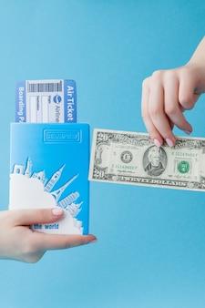 Paszport, dolary i bilet lotniczy w kobiecej dłoni na niebiesko