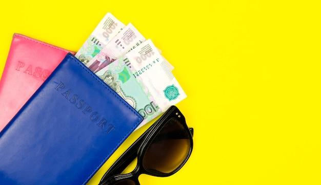 Paszport i pieniądze z okularami przeciwsłonecznymi na solidnej ścianie. pojęcie podróży. skopiuj lokalizację tekstu.