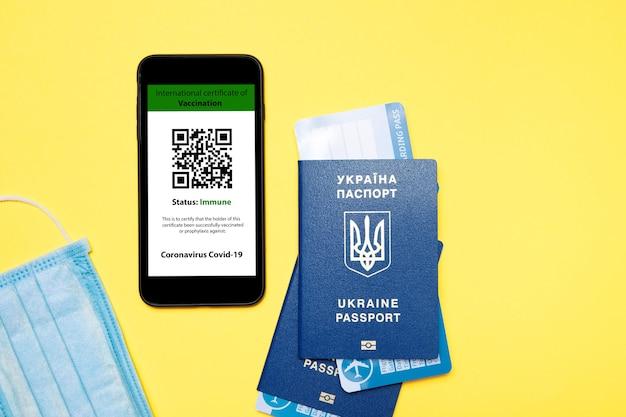 Paszport i smartfon z cyfrowym zaświadczeniem o szczepieniu przeciwko chorobie covid-19.