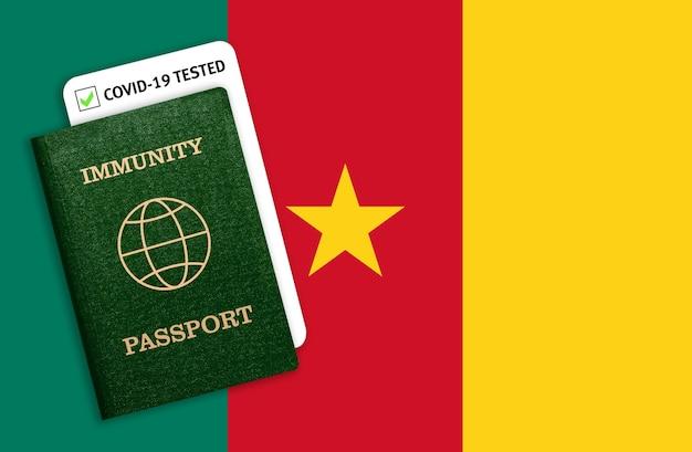 Paszport immunitetu umieszczony nad flagą narodową kamerunu.
