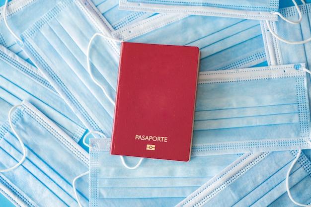 Paszport na niebieskim tle pełen masek chirurgicznych protokoły bezpieczeństwa podróżowania koronawirus