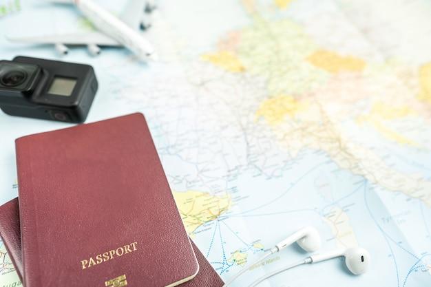 Paszport na tle mapy. planowanie podróży. widok z góry akcesoriów podróżnika z samolotem, aparat na mapie świata.
