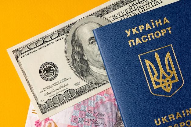 Paszport obywatela ukraińskiego z dolarami amerykańskimi i banknotami hrywny ukraińskiej w środku. wyjazd za granicę, koncepcja kursu walutowego