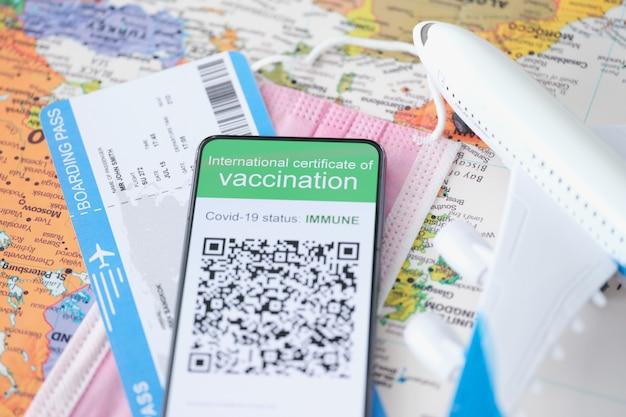 Paszport szczepień przeciw covid jest wyświetlany na smartfonie obok choroby poszczepiennej na bilecie lotniczym