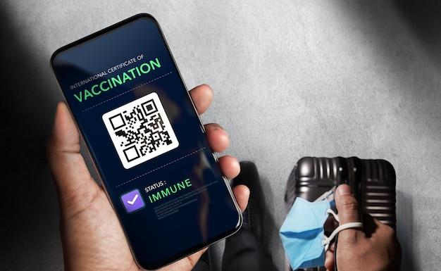 Paszport szczepionek zdrowotnych na koronawirusa lub covid-19. podróżny korzystający z telefonu komórkowego z szczepieniem w stanie odpornościowym w celu certyfikowanego międzynarodowego podróżowania na lotnisku