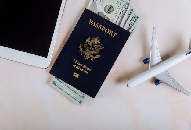 Paszport usa i banknoty dolara z modelu samolotu, spiralny notatnik na tablecie dotykowym tabletu urządzenia