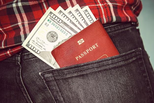 Paszport w tylnej kieszeni dżinsów z amerykańskimi dolarami. koncepcja podróży. kieszonkowe w mojej tylnej kieszeni. wydatki z kieszeni. sto dolarów