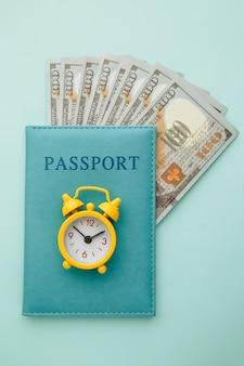 Paszport z banknotami pieniędzy i budzikiem