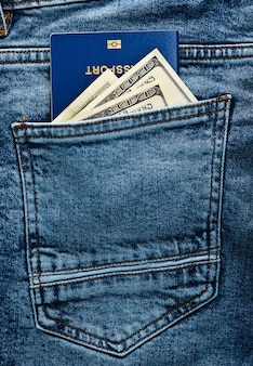 Paszport z banknotami stu dolarowymi w tylnej kieszeni dżinsów. podróżował koncepcja lub imigracja.