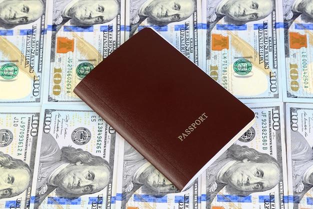 Paszport z dużo sto dolarów banknotów tła