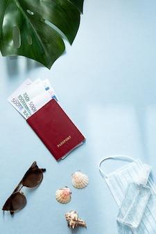 Paszport z pieniędzmi, medyczną maskę na twarz i środek do dezynfekcji rąk, okulary przeciwsłoneczne, muszle i liść palmowy monstera.
