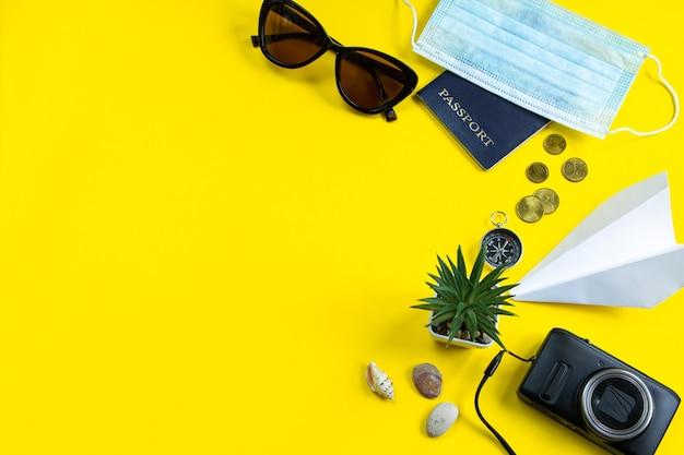 Paszportowa maska medyczna i okulary przeciwsłoneczne na żółtym tle koncepcja bezpiecznej podróży