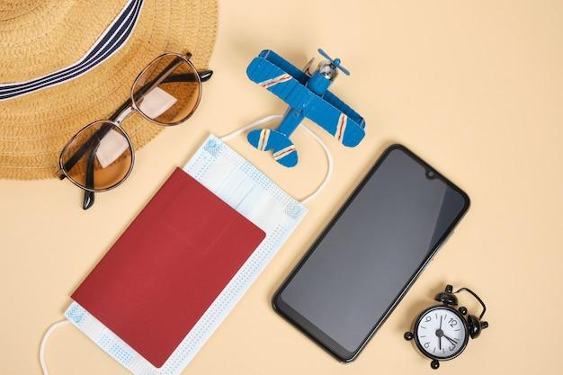 Paszportowy kapelusz okulary przeciwsłoneczne budzik i samolot zabawkowy na beżowym tle widok z góry płaski widok z góry na ochronę przed wirusem koronowym