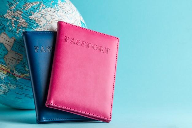 Paszporty i kula ziemska na niebieskim tle. podróż, wakacje, rekreacja. wakacje, turystyka, podróżnik.
