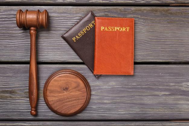 Paszporty i młotek na drewnie. koncepcja deportacji płasko świeckich widok z góry.