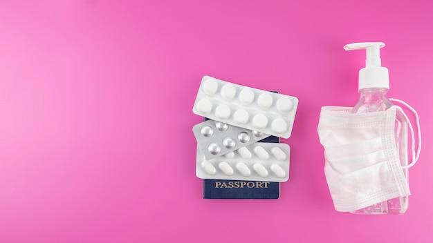 Paszporty, maska medyczna, środki antyseptyczne i pigułki. covid-19 i koncepcja podróży. widok z góry, miejsce na tekst