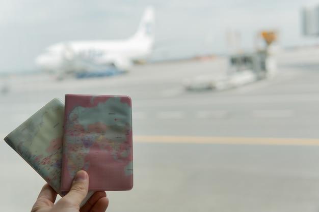 Paszporty w ręku na tle samolotu.