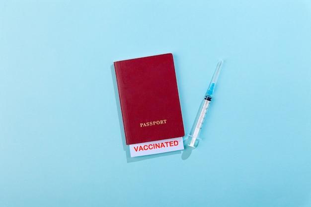 Paszporty z pieczęcią szczepień na pustej strzykawce ze szczepionką na niebiesko
