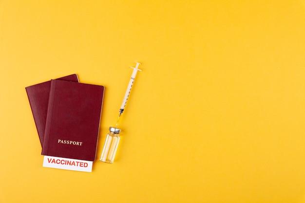 Paszporty z zaszczepioną pieczęcią na pustej butelce strzykawki ze szczepionką na żółtym tle