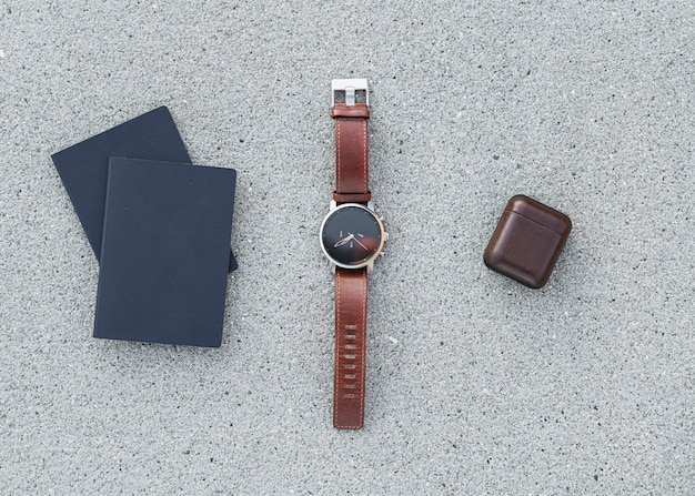 Paszporty z zegarkiem i wkładkami dousznymi na tle betonu