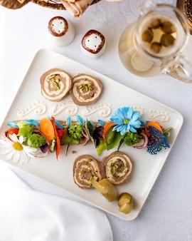 Pasztet ozdobiony ogórkami i marchewką oraz dzbanek z kompotowym widokiem z góry