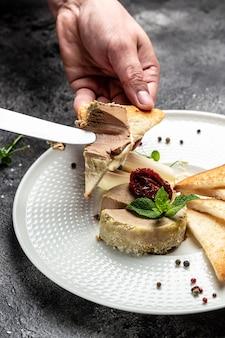 Pasztet z wątroby. męskie dłonie rozmazują domową pastę na chleb tostowy. świeży pasztet domowej roboty. tło przepis żywności. ścieśniać.