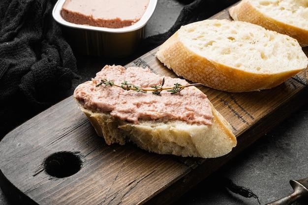 Pasztet z wątroby na zestawie tostowym, na czarnym ciemnym tle kamiennego stołu