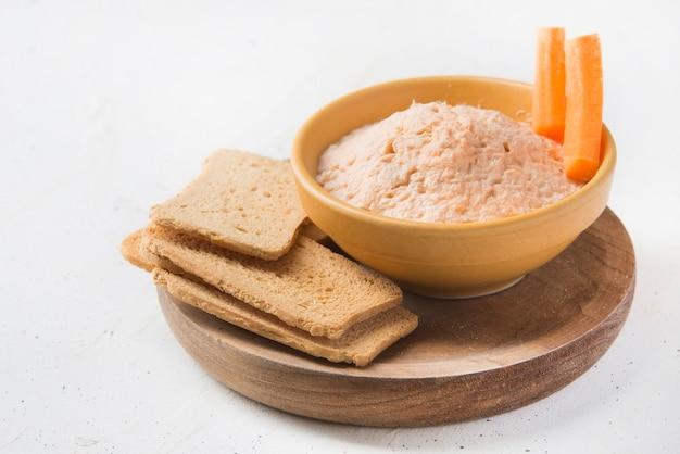 Pasztet z wędzonym łososiem i miękkim serem z ciemnym chlebem i marchewką na białym tle