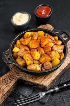 Patatas bravas, pikantne ziemniaki, hiszpańskie danie ze smażonym ziemniakiem i pikantnym sosem czosnkowym. czarne tło. widok z góry.