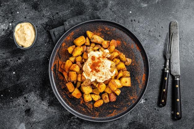 Patatas bravas, tradycyjne hiszpańskie tapas, pieczony ziemniak z pikantnym sosem pomidorowym. czarne tło. widok z góry.