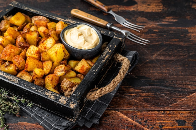 Patatas bravas tradycyjne hiszpańskie tapas z ziemniakami. ciemne drewniane tło. widok z góry. skopiuj miejsce.