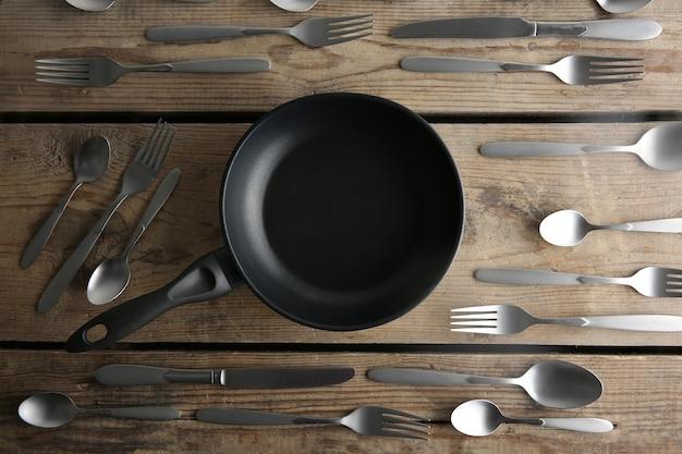 Patelnia i srebrne sztućce na drewnianym stole, widok z góry