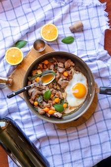 Patelnia jajka sadzone, wieprzowina, melasa, papryka i bazylia, z serwetką na drewnianej powierzchni stołu, widok z góry