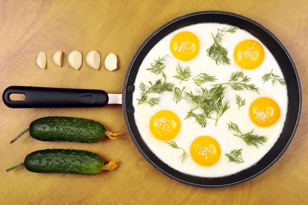 Patelnia na stole ze smażoną jajecznicą z koperkiem i ogórkiem, czosnkiem. zdrowe obfite śniadanie