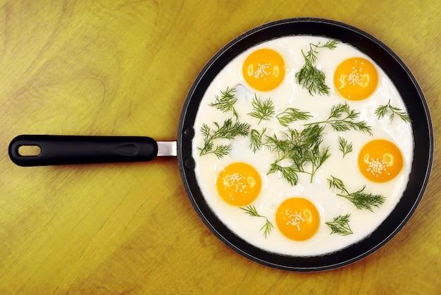 Patelnia na stole ze smażoną jajecznicą z koperkiem i sezamem. zdrowe obfite śniadanie