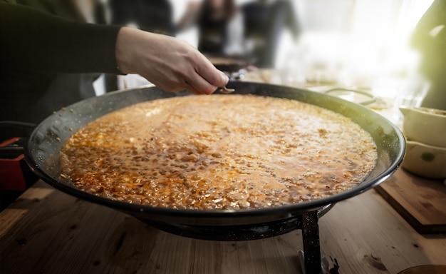 Patelnia paella z tradycyjnymi hiszpańskimi potrawami zwykle przygotowywanymi z ryżu, mięsa, owoców morza.