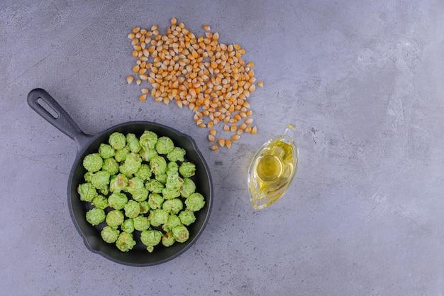 Patelnia pełna cukierków popcornowych obok pojemnika z olejem i niewielką porcją ziaren kukurydzy na marmurowym tle. zdjęcie wysokiej jakości