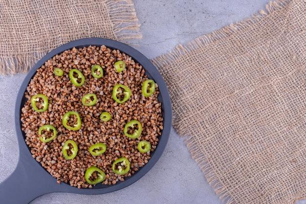 Patelnia pełna gotowanej kaszy gryczanej z posypką z papryki na marmurowym tle. zdjęcie wysokiej jakości