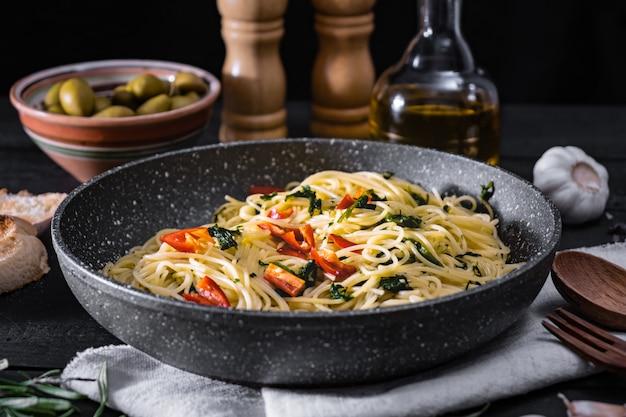 Patelnia ugotowanego włoskiego makaronu. tradycyjny posiłek spaghetti z warzywami i oliwkami na czarnej powierzchni rustykalnej