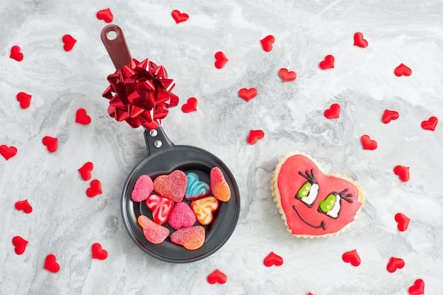 Patelnia z cukierkami w kształcie serca i ciasteczkami na świątecznym