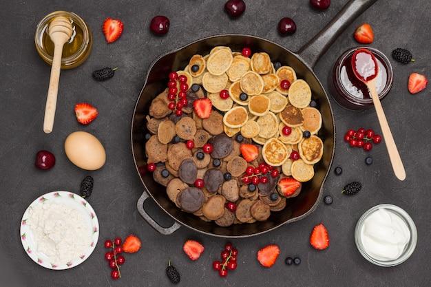 Patelnia z naleśnikami zbożowymi. mąka, jogurt jagodowy, masło, konfitura miodowa. przekąska zdrowej diety. leżał na płasko