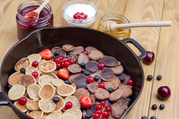 Patelnia z naleśnikami zbożowymi. mąka, jogurt jagodowy, masło, konfitura miodowa. przekąska zdrowej diety. ścieśniać