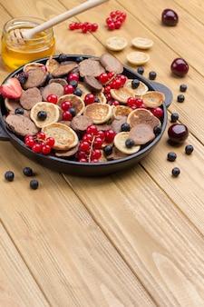 Patelnia z naleśnikami zbożowymi. mąka, jogurt jagodowy, masło, konfitura miodowa. przekąska zdrowej diety. widok z góry. skopiuj miejsce