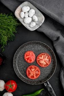 Patelnia z pomidorami z jajkami i koprem włoskim na czarnym stole
