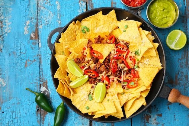 Patelnia z smacznymi nachos, mięsem mielonym i chili na drewnianym stole