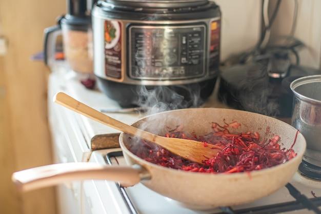 Patelnia z warzywami do pierwszego dania na tle multi-cooker. gotowanie barszczu w urządzeniu wielofunkcyjnym.