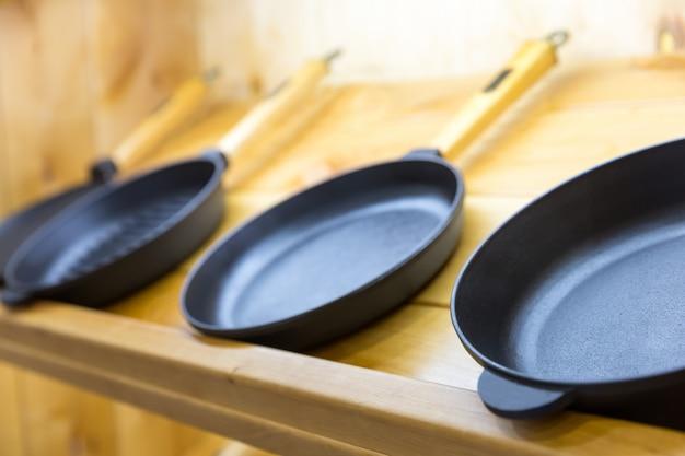 Patelnie na drewnianej półce zbliżenie, narzędzia do gotowania. dekoracja kuchni, żelazne naczynie